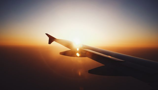 Image of a luxury private jets wing in flight with sunset behind it