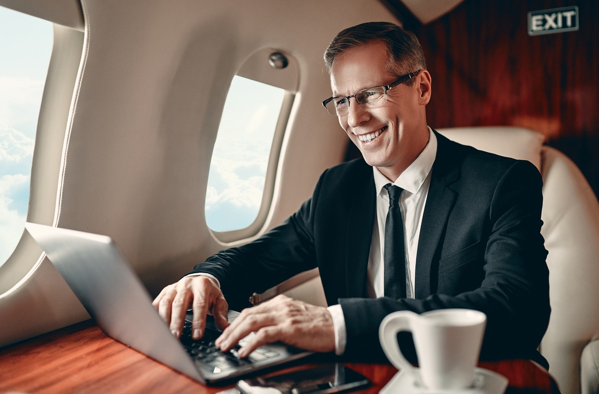 Senior businessman in suit is working on a laptop while flying in private jet.